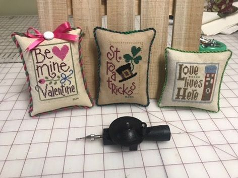 My husband bought me this little cording tool for Christmas, and after watching some online videos I learned how to use it to put cording around some of my finishes. And I have to say that you can cover up a multitude of mistakes with the cording.  Some of the shown pieces here are some that I have stitched a few years ago and just now getting around to actually finishing them.