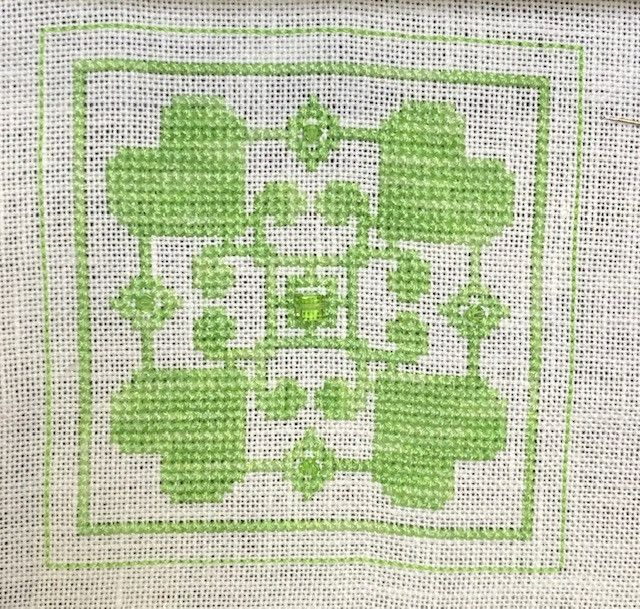 "Here is my stitching of the ""Stitch This"" chart from the August newsletter.  I have used some Peridot Swarovski crystals and stitched an outline so that I can make this into my second ever biscornu!"